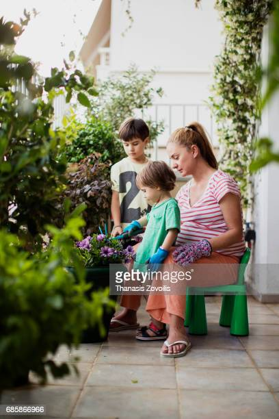 Pregnant mother gardening with her kids