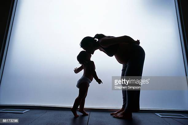 Pregnant mother kissing daughter
