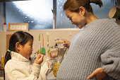Pregnant mother making drink with her daughter in her kitchen