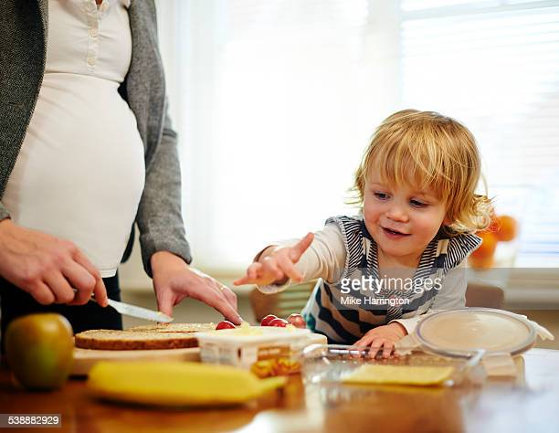 Pregnant mother making sandwiches with daughter