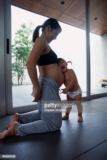 Pregnant mother with daughter embracing belly