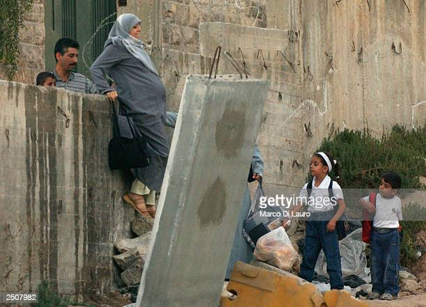 A pregnant Palestinian woman climbs over a wall of cement barricades erected by Israel on September 18 2003 from east Jerusalem into the village of...