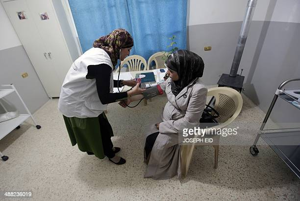 A pregnant Syrian refugee woman undertakes a checkup at a clinic managed by the French nongovernmental organisation Medecins Sans Frontieres in the...