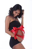 Pregnant tanned skin Indian woman Tummy belly with red ribbon gift,  Smile maternity in black bra pant