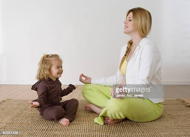 Pregnant woman and girl in yoga pose