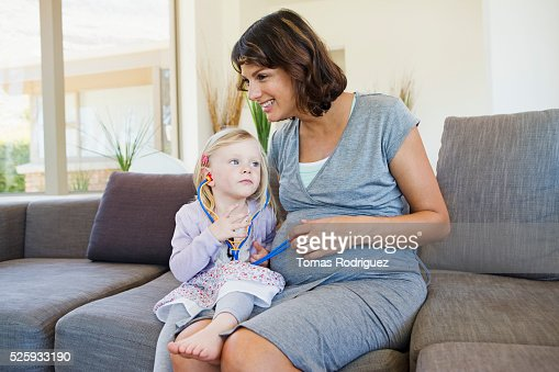 Pregnant woman and girl (2-3) playing in living room : Foto de stock