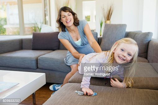 Pregnant woman and girl (2-3) playing in living room : Stock-Foto