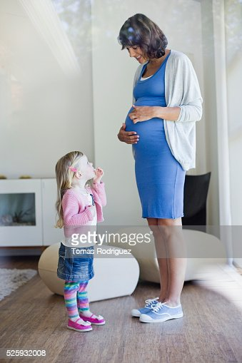 Pregnant woman and girl (2-3) standing in living room : Photo