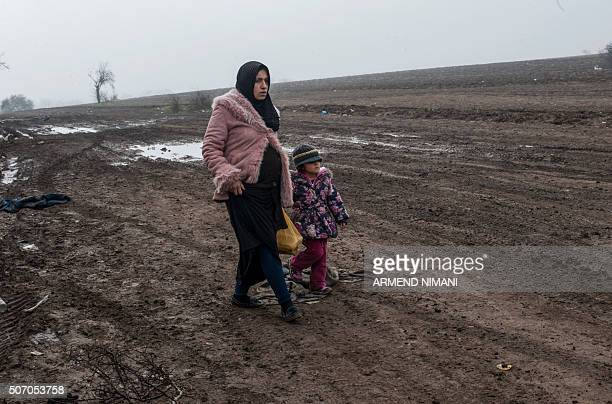 A pregnant woman and her child walk through a field along with other migrants and refugees after crossing into Serbia via the Macedonian border near...