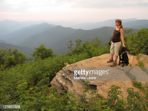 Pregnant woman and her dog hiking in mountains