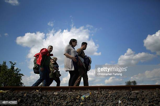 A pregnant woman and her family cross the border from Serbia into Hungary along the railway tracks close to the village of Roszke on September 6 2015...