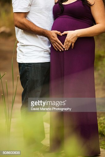 A pregnant woman and her man holding belly : Stock Photo