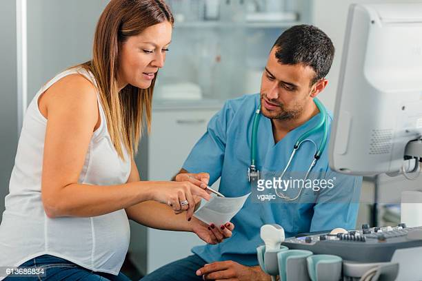 Pregnant Woman And Male Doctor In A Consultation.