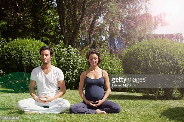 Pregnant woman and man doing gymnastic exercises in garden