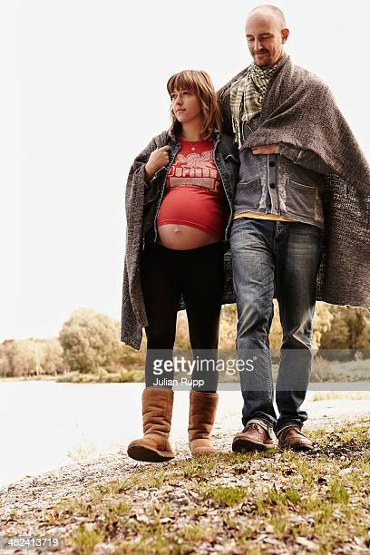 Pregnant woman and partner walking beside river