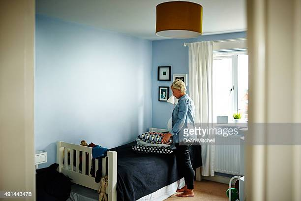 Pregnant woman arranging cushions on bed