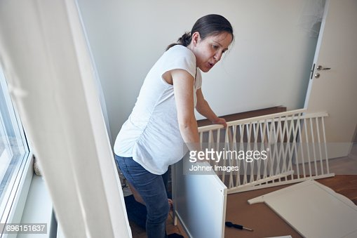 Pregnant woman assembling cot