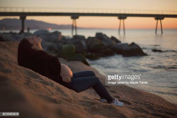 Pregnant woman at sunset in the beach