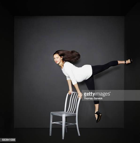Pregnant woman balanced between chair and wall