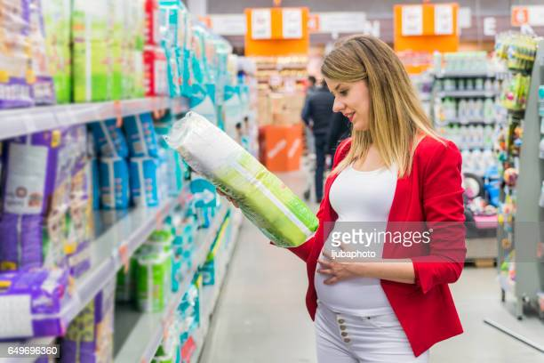 Pregnant woman buying diapers at the supermarket