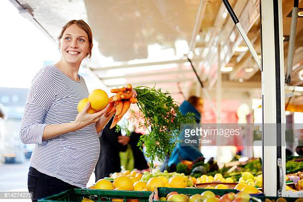 Pregnant woman buying fruit and veggies at market