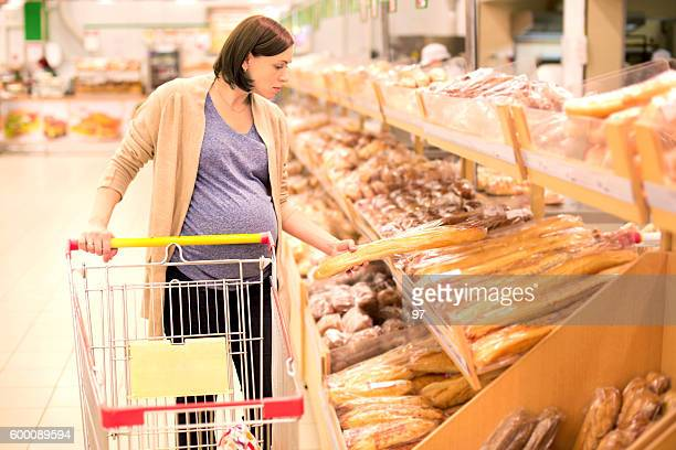 pregnant woman buys bread at the supermarket