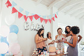 Group of multiracial women at a baby shower. Pregnant woman celebrating baby shower with female friends at home.