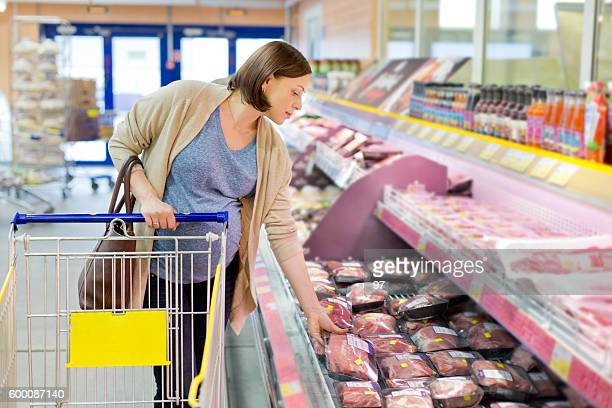 pregnant woman chooses meat in the store