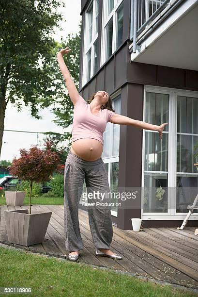 Pregnant woman dancing posing happy terrace
