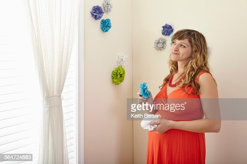 Pregnant woman decorating nursery with paper flowers