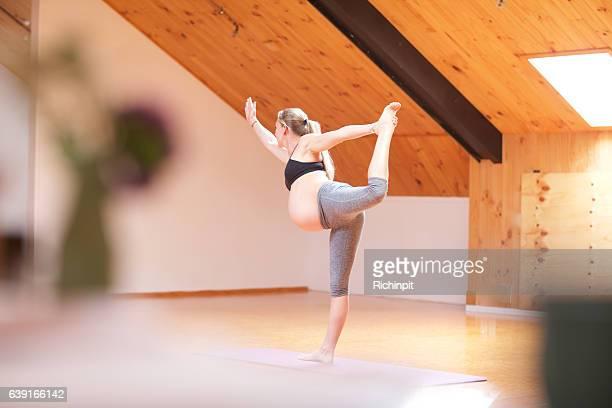 Pregnant woman does a balancing yoga pose