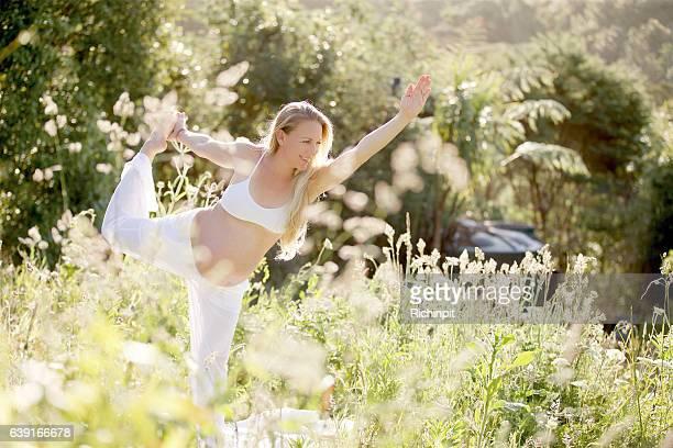 Pregnant woman does yoga in a garden