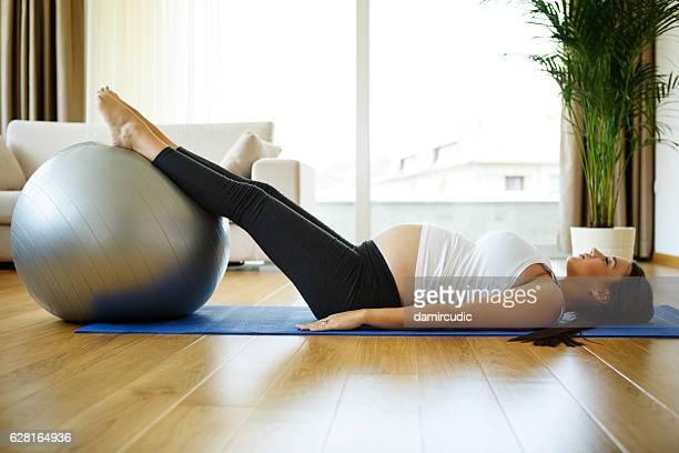 Femme enceinte heureuse, faire des exercices de pilates