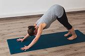 Pregnant woman doing prenatal yoga in a studio in downward facing dog posture