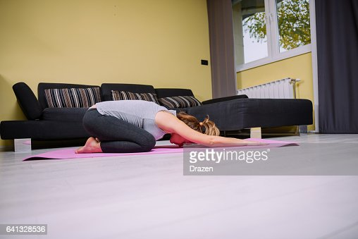 Pregnant woman doing relaxation exercises and stretching at home