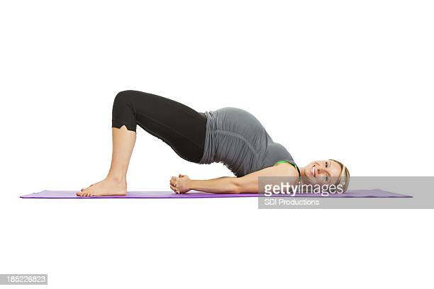 Pregnant woman doing stretching exercise on yoga mat