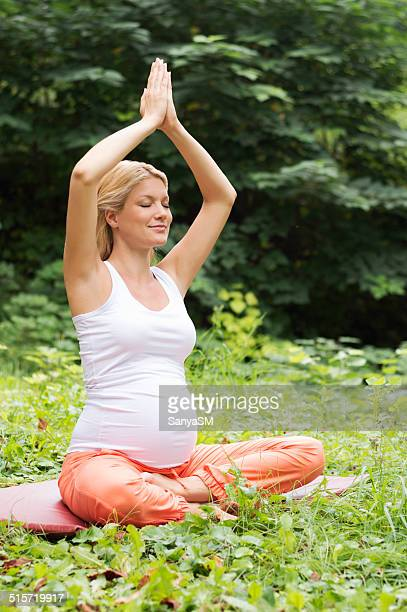 Pregnant woman doing yoga in nature
