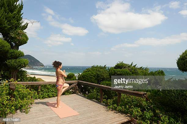 Pregnant woman doing Yoga on the beach side