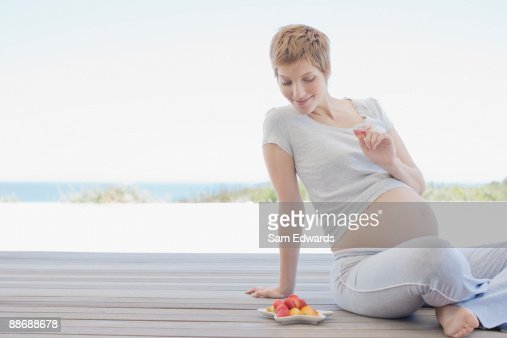 Pregnant woman eating fruit on deck : Stock Photo