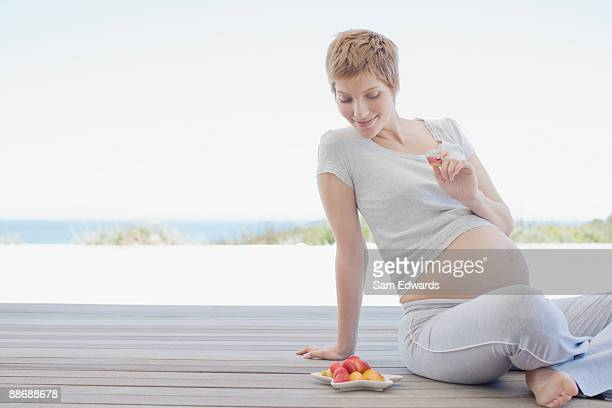 Pregnant woman eating fruit on deck