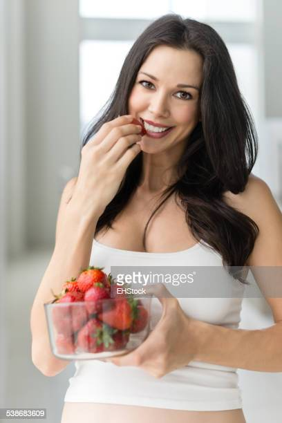 Pregnant Woman Eating Strawberries in Home
