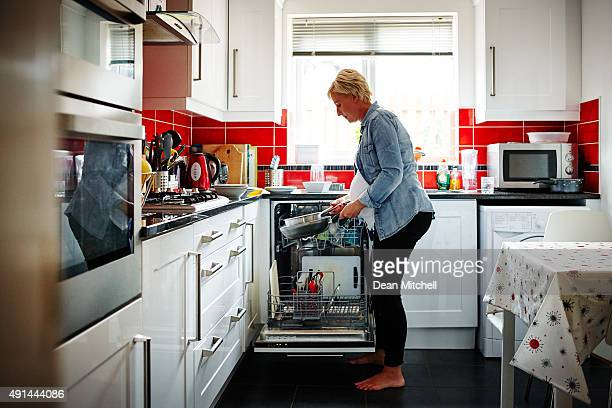 Pregnant woman emptying the dishwasher