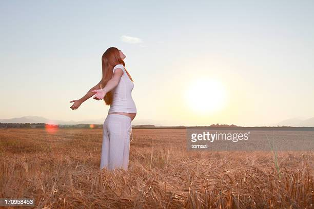 Pregnant woman enjoying in the field