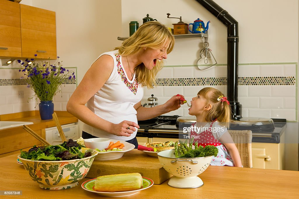 Pregnant woman feeds healthy food to her 3 year old daughter in their kitchen. : Stock Photo