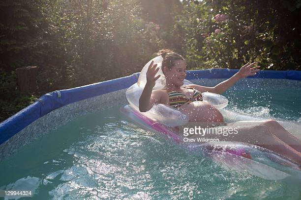 Pregnant woman floating in pool