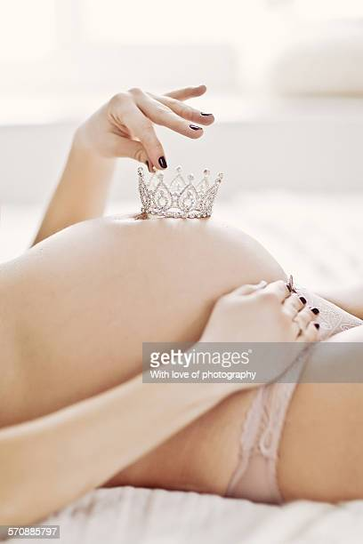 Pregnant woman holding a crown on belly