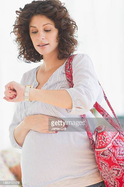 Pregnant woman holding bag, looking at watch