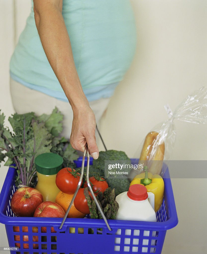 Pregnant Woman Holding Basket Of Groceries Stock Photo ...