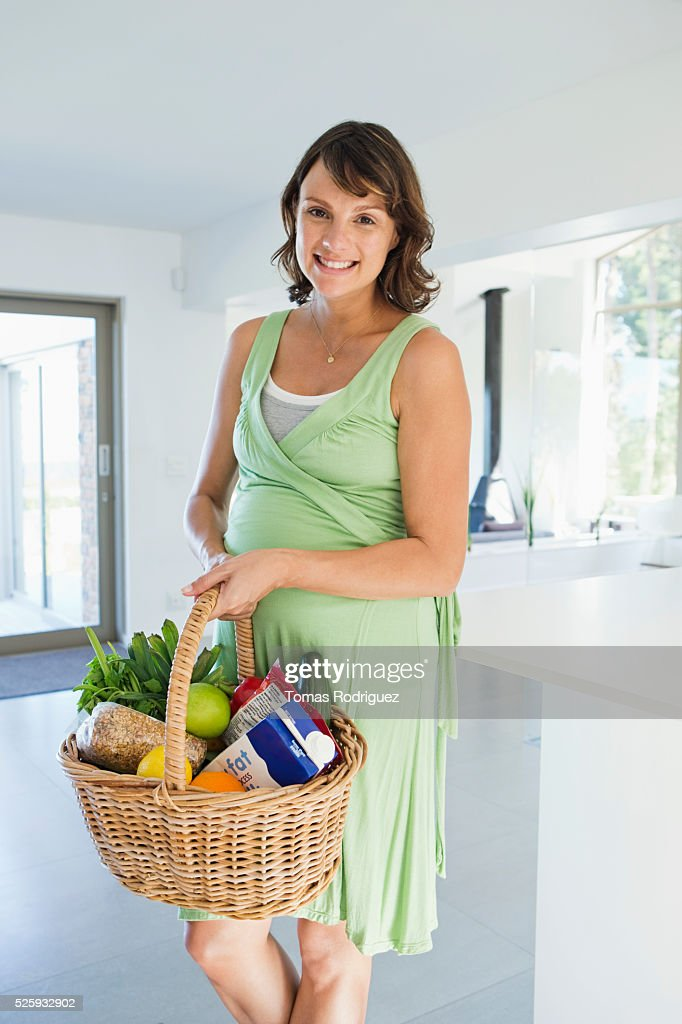 Pregnant woman holding basket with vegetables in kitchen : Stock Photo