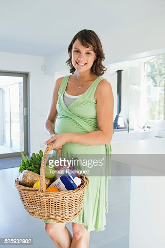 Pregnant woman holding basket with vegetables in kitchen : Foto stock